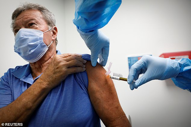 About half of respondents said they would be immunized if they were paid $100 or if they could get it at a drive-thru clinic. Pictured:A volunteer is injected with a vaccine as he participates in a coronavirus vaccination study in Hollywood, Florida, September 24
