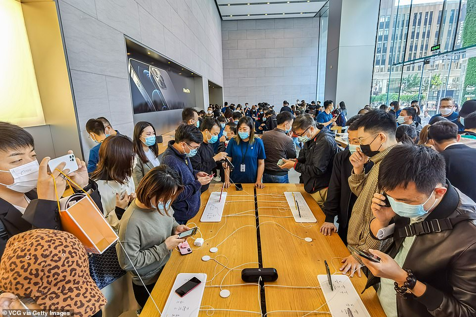 Inside the Shanghai store customers try out iPhone 12 smartphones. Apple launch day appears to mean social distancing has gone out the window