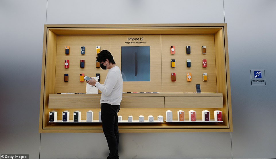 Jun, the first customer in Sydney's Apple Store, enjoys the feel of the new iPhone 12, which is notable for itsflat edges unlike the curved edges of recent iPhone models