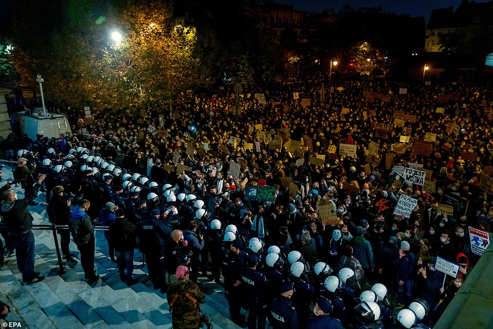 Two rows of police are seen blocking off protestersin front of the Christ the King Archcathedral in Katowice, southern Poland