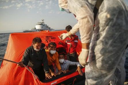 Turkish coastguard officers talk to migrants on a liferaft
