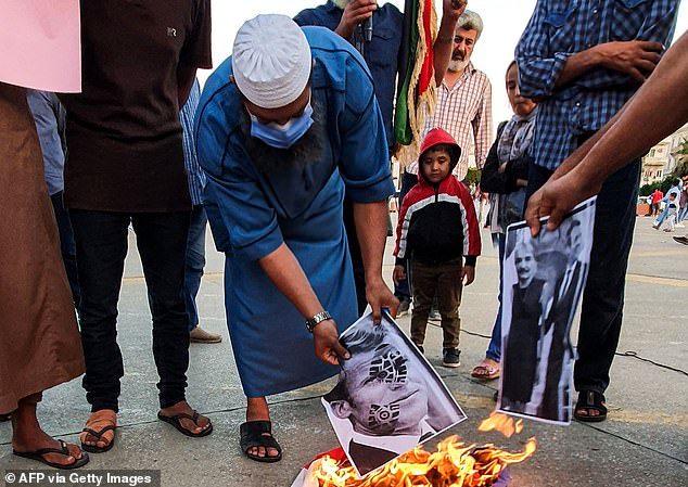 Demonstrators set fire to pictures of Macron in Tripoli, one of which includes the face of Libyan general Khalifa Haftar photoshopped onto a woman's body