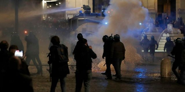 Police uses a water cannon to disperse protestors as smoke billows during a protest against the government restriction measures to curb the spread of COVID-19, in Rome on Tuesday. (AP Photo/Alessandra Tarantino)