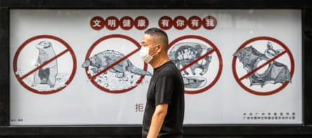 A man walks past a poster warning people that consuming wildlife is illegal, in Guangzhou, Guangdong province, China.