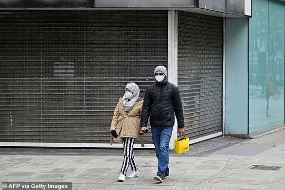 A couple wearing protective face coverings pass a closed shop in Oxford Street in London, on October 17. Last week it was revealed footfall in central London has collapsed by 60 per cent compared to 2019, while the figure for regional cities is down by around 50 per cent