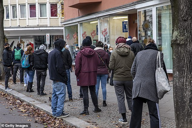 People queue outside a doctor's surgery in Berlin to be tested today, with the second wave in full swing in Germany
