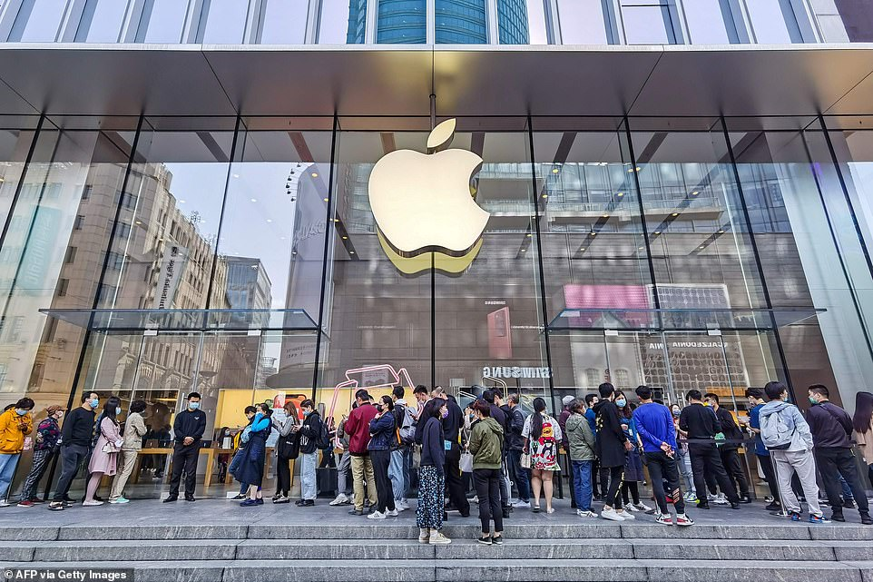 People wait outside an Apple store as the new iPhone 12 series launches in Shanghai, where crowds were reportedly smaller than last year