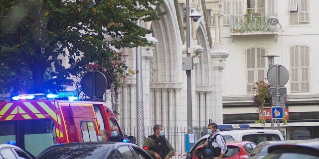 French policemen stand next to Notre Dame church after a knife attack, in Nice, France, Thursday, Oct. 29, 2020. French anti-terrorism prosecutors are investigating a knife attack at a church in the Mediterranean city of Nice that killed three people and injured several others. (AP Photo/Alexis Gilli)