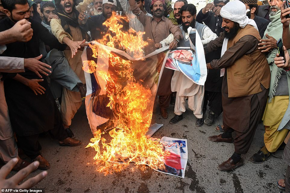 Muslims demonstrators burn posters of Emmanel Macron during a protest in Quetta, Pakistan, on Thursday