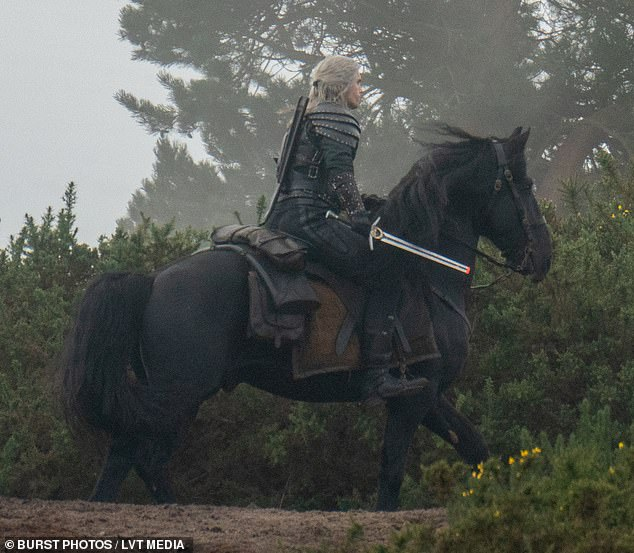 And, action! Henry Cavill prepared for battle as he donned armour and wielded a sword while on horseback to film scenes for The Witcher's second season in Surrey on Wednesday