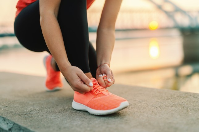 Close up of sporty woman tying shoelace while kneeling outdoors