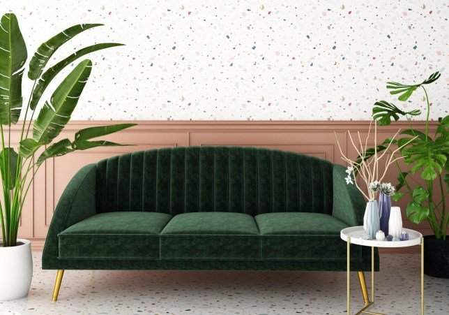 green velvet sofa next to pink wall, plants, and a coffee table