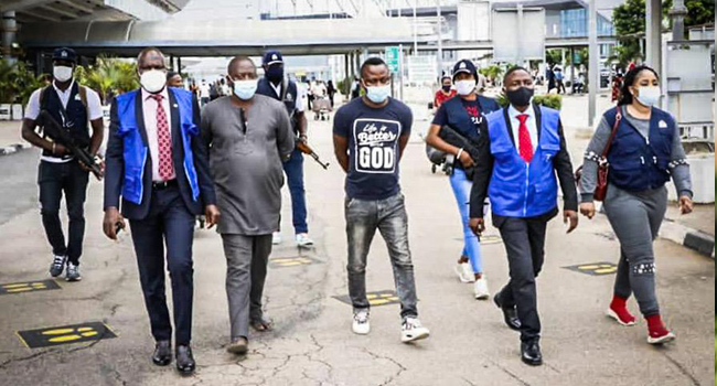 This image, published on Interpol's website on November 25, 2020, shows two suspects being led way by security officials..