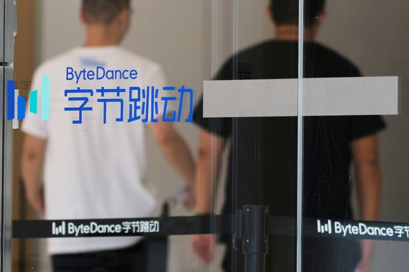 © Reuters. People walk past a logo of Bytedance, which owns short video app TikTok, at its office in Beijing