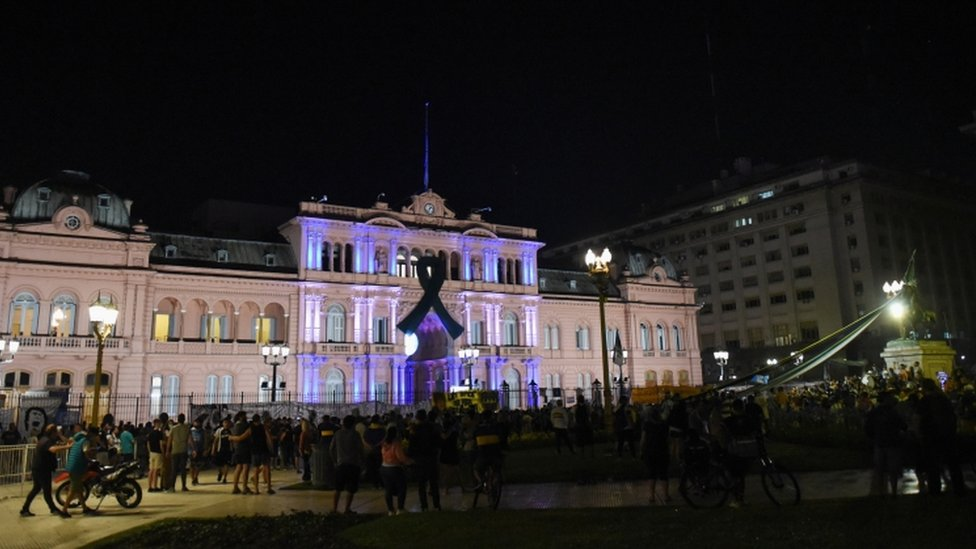 People gather outside the Casa Rosada presidential palace ahead of the wake of soccer legend Diego Maradona, in Buenos Aires, Argentina