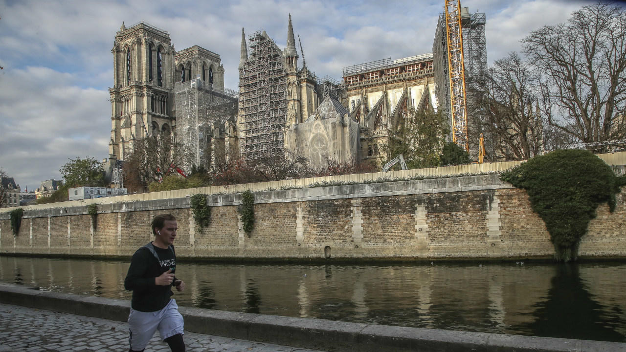 A man jogs along the Seine river next to Notre-Dame Cathedral, on November 25, 2020, in Paris.