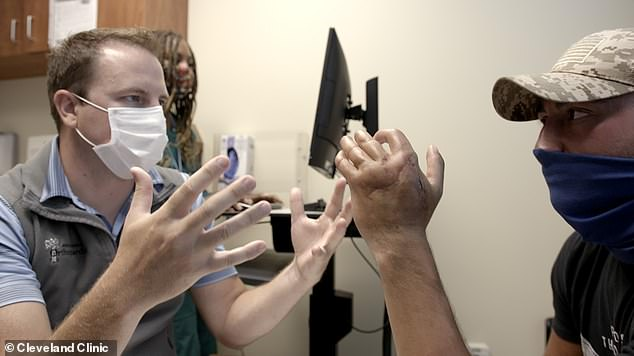After four more surgeries and several weeks of therapy, Brittain says he has almost regained complete strength in his hand. Pictured: Luke during a follow-up with Dr Lanzinger