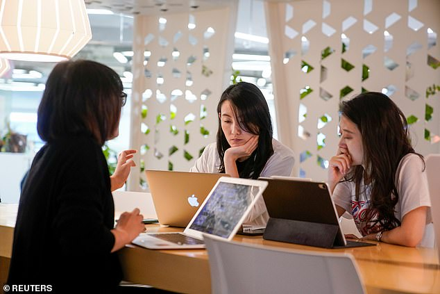 In response to the public¿s criticism, the Chinese company explained that the timers were installed to solve the site¿s problem of ¿toilet shortage¿. In this file photo, three workers are seen having a meeting at an office in Hangzhou, Zhejiang province of east China on Thursday