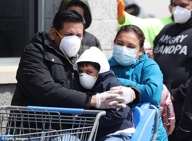 Because masks reduce the amount of particles inhaled, two doctors say face coverings could be a way to generate immunity until there is a vaccine. Pictured:People wearing masks and gloves wait to enter a Walmart in Uniondale, New York, April 17
