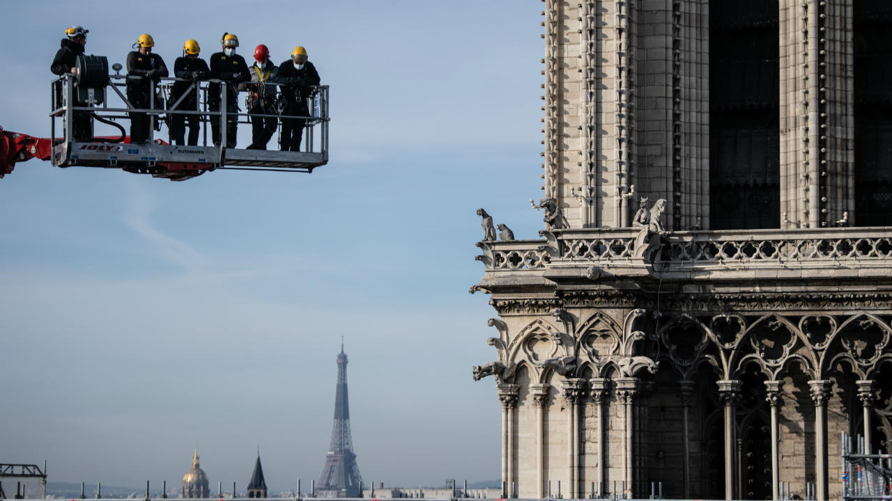Workers on a crane look at Notre-Dame Cathedral site on November 24, 2020 in Paris.