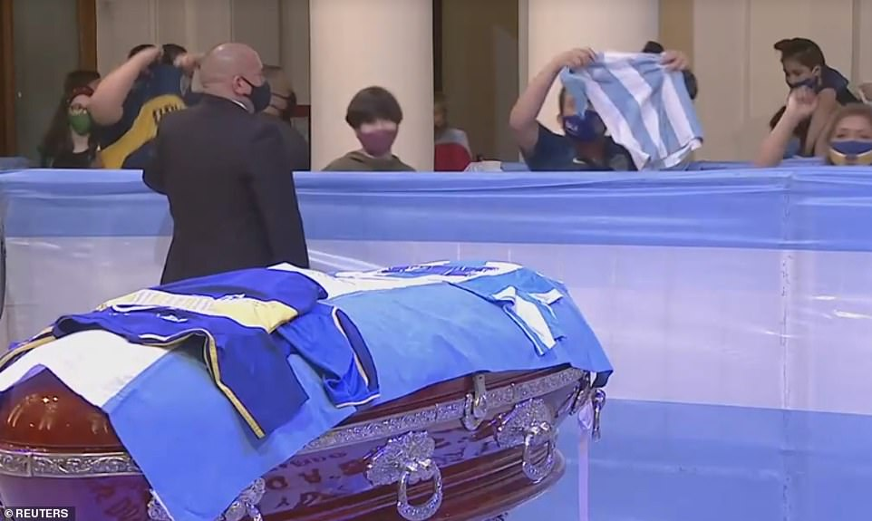 On display: Mourners clapped, pumped their fists and threw football shirts and flags as they filed past the coffin at the presidential palace where it will lie in state for three days