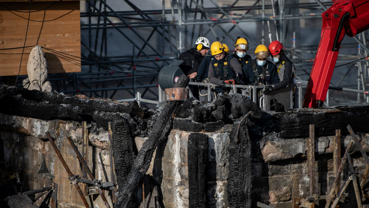Notre-Dame Cathedral restoration workers on a crane examine burnt woodwork on November 24, 2020.