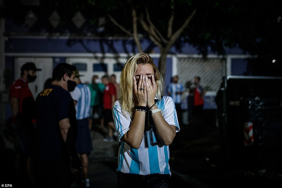 A fan wearing an Argentina number 10 shirt in tribute to Maradona cries at a gathering outside the Diego Armando Maradona Stadium in Buenos Aires where the football legend began his career as a young player