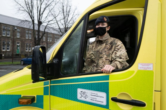 CARDIFF, WALES - DECEMBER 23: A member of the military poses for a photograph with an ambulance at Maindy Barracks on December 23, 2020 in Cardiff, Wales. The Welsh Ambulance Service has called on the army to help as it deals with acute pressure on its service. More than 90 soldiers will be drafted in from today to help drive their emergency vehicles as the second wave of the coronavirus pandemic continues to take hold on the NHS. Members of the 9th Regiment Royal Logistic Corps, 1st Armoured Medical Regiment, RAMC (Royal Army Medical Corps) and the 4th and 5th Armoured Medical Regiment will provide assistance. Wales has had more Covid-19 cases in the last seven days relative to its population than any other country in the world except Lithuania. (Photo by Matthew Horwood/Getty Images)