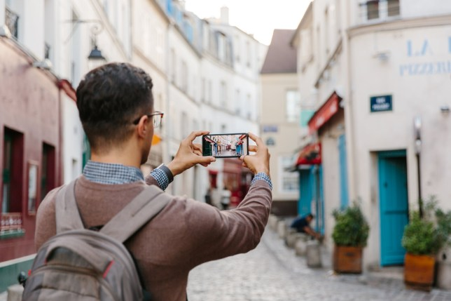 Tourist taking pictures on his phone in France