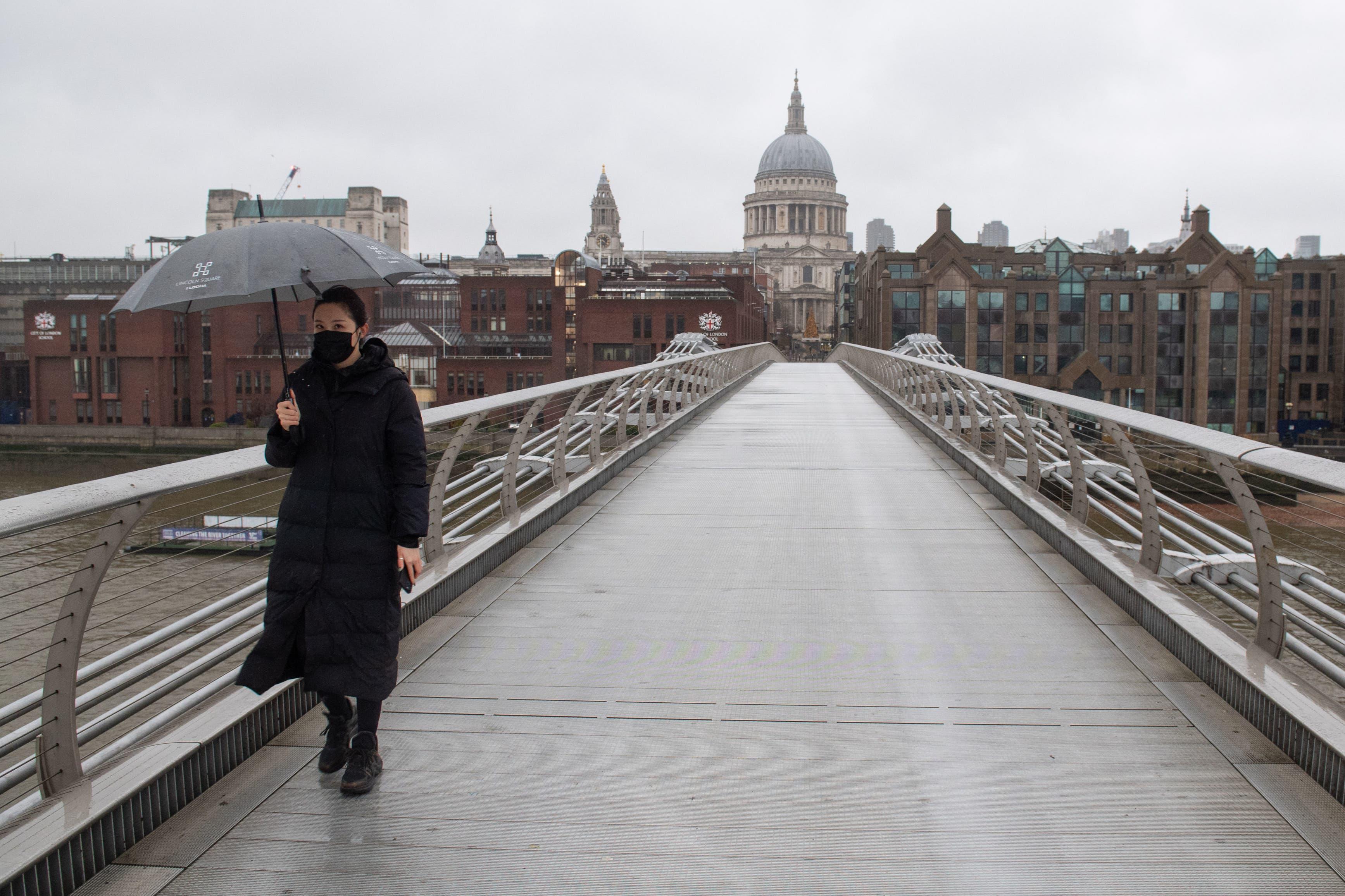 <p>A woman crosses a quiet Millennium Bridge in London. Prime Minister Boris Johnson cancelled Christmas.</p>