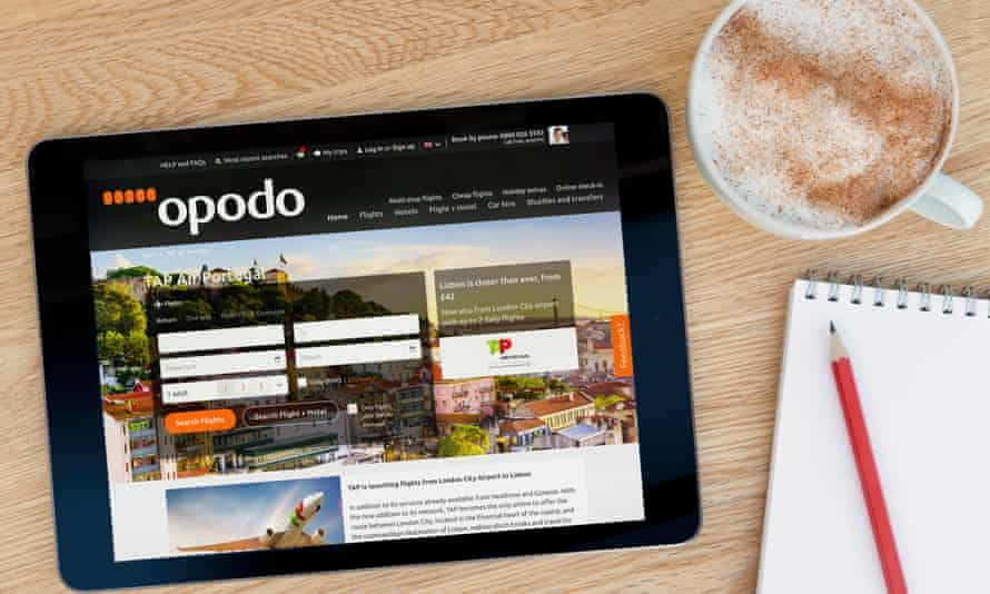The Opodo website on a tablet computer lying next to a cup of coffee on a table