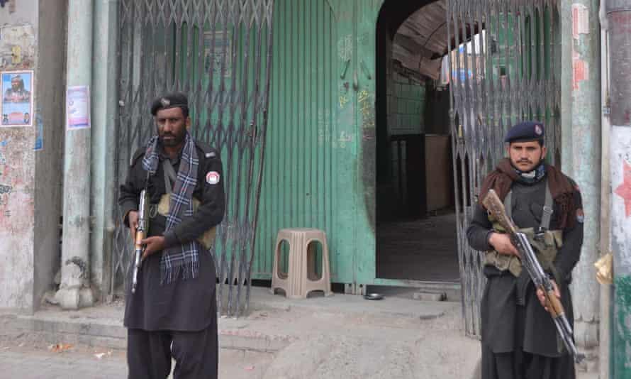 Pakistani security officials guard a temple following attacks on Hindu temples in Larkana, in Quetta, Pakistan