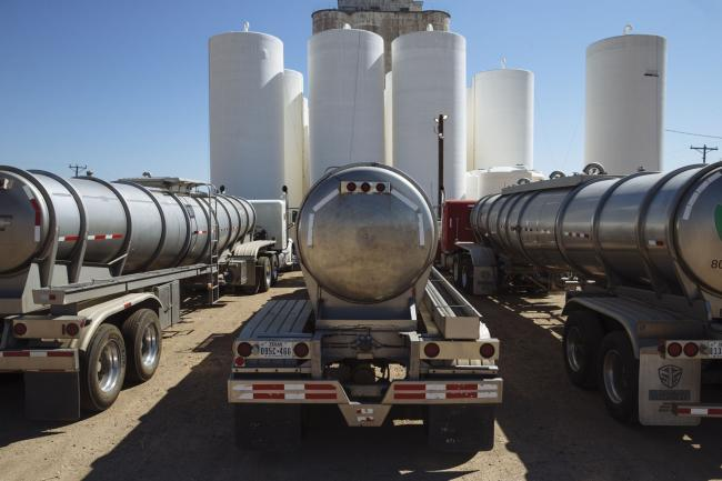 © Bloomberg. Tanker trucks sit in front of storage silos in Sunray, Texas, U.S., on Saturday, Sept. 26, 2020. After all the trauma the U.S. oil industry has been through this year -- from production cuts to mass layoffs and a string of bankruptcies -- many producers say they're still prioritizing output over reducing debt. Photographer: Angus Mordant/Bloomberg