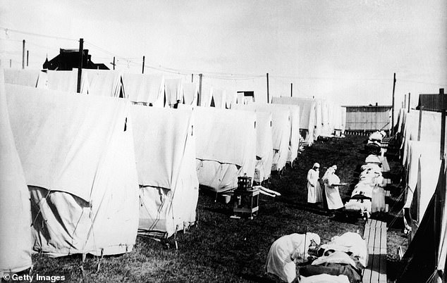 Masked doctors and nurses treat  Spanish flu patients lying on cots and in outdoor tents at a hospital camp in America, 1918. The Spanish flu was much more deadly than coronavirus and killed 50million people worldwide