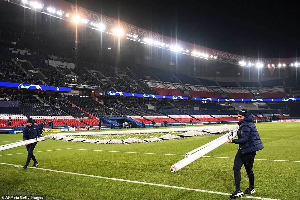 Parc des Princes stadium workers remove the goalposts from one end of the pitch after the match was suspended