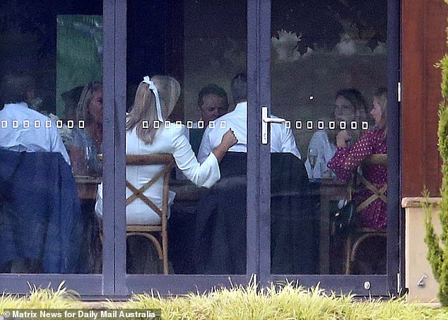 All smiles: The limited number of guests appeared in high spirits as they sat with the newlyweds, with Sam seen putting a supportive hand on her new husband's back