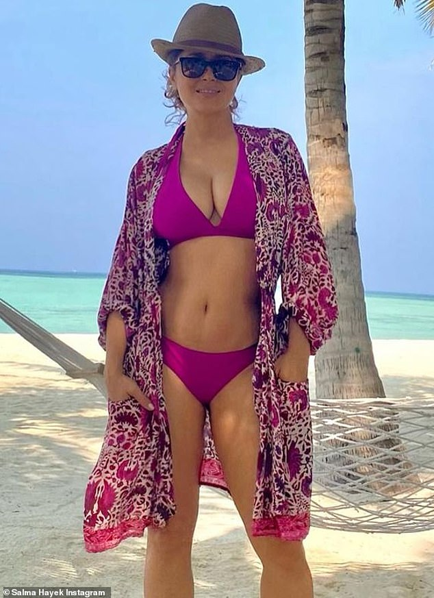 Grateful for being healthy:Posing up by the water, the agelessly beautiful 54-year-old showed off her ample cleavage and enviably taut midriff in a clinging purple two-piece
