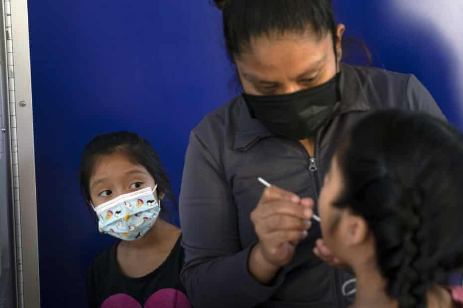 Katie Ramirez, left, watches as her mother, Claudia Campos, swabs the mouth of another daughter, Hailey, at a testing site in Los Angeles this month.