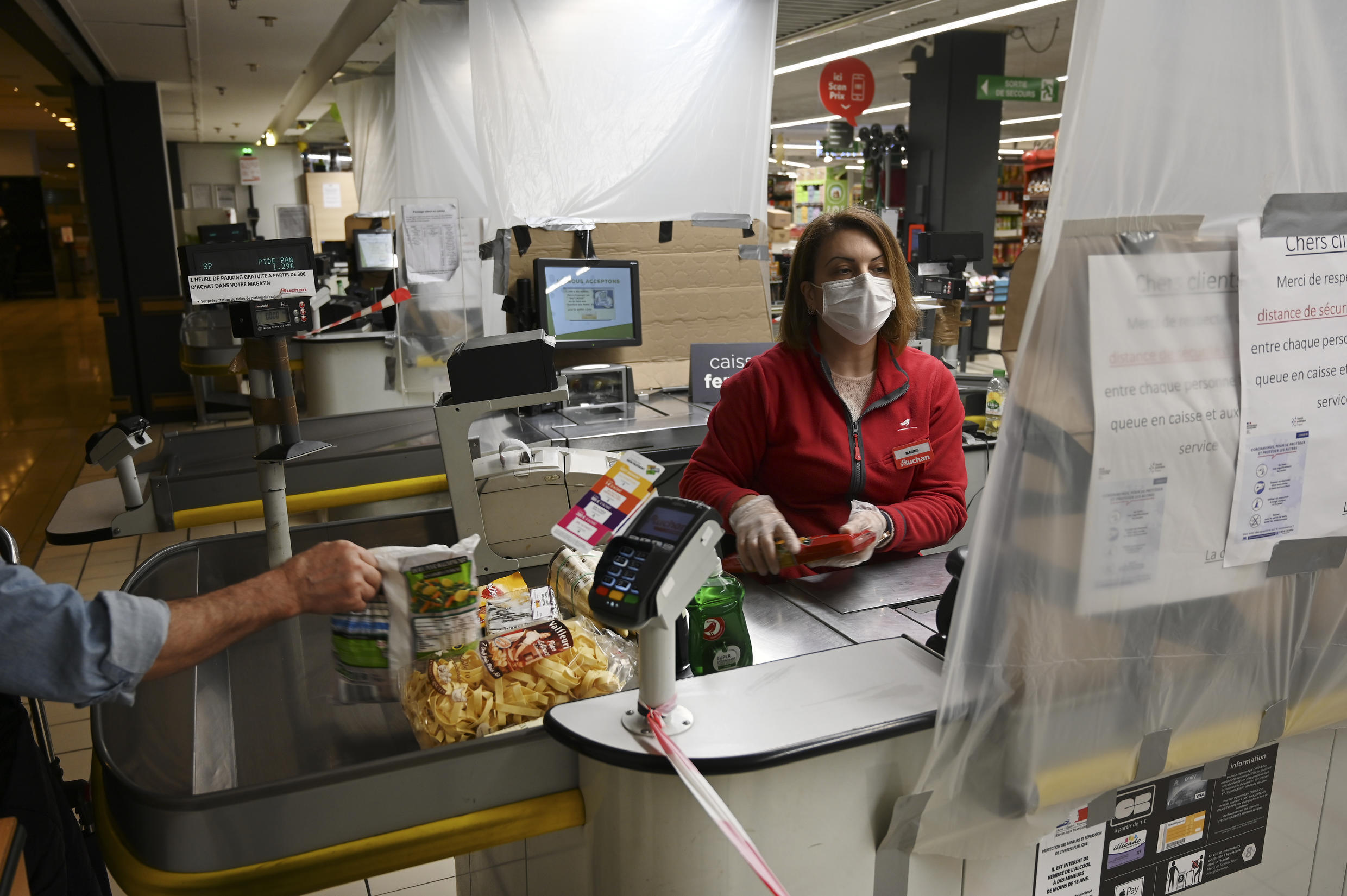 A cashier protected by a plastic tarp in a supermarket in eastern France.