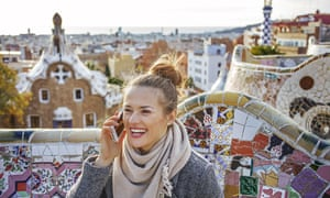 Young woman at Guell Park in Barcelona, Spain speaking on phone