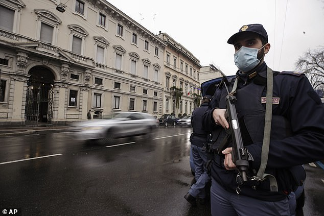 A police officers armed with a machine-gun stops vehicles in Milan on Thursday to check people are not travelling long-distance in breach of Covid rules