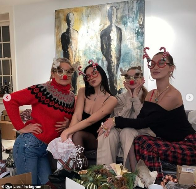 Festive beauties:The star also cosied up to Gigi, Bella and their mum Yolanda in a fun picture which saw the ladies do novelty festive glasses