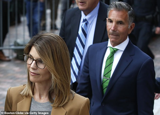 Ouch: The 57-year-old fashion designer is 'having a rough time in prison' according to a source for Us Weekly on Wednesday, as he is seen with wife Lori Loughlin in Boston in April 2019
