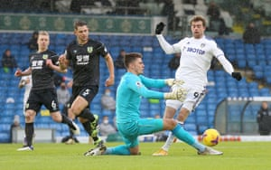 Nick Pope of Burnley tackles Patrick Bamford of Leeds United leading to a penalty.
