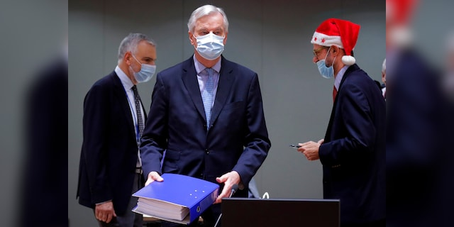 A colleague wears a Christmas hat as European Union chief negotiator Michel Barnier, center, carries a binder of the Brexit trade deal during a special meeting of Coreper, at the European Council building in Brussels, on Dec. 25. (AP)