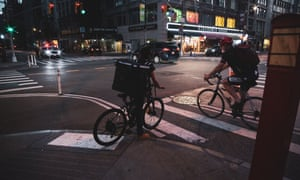Delivery workers at night on 5th Ave during the coronavirus outbreak, in Manhattan.