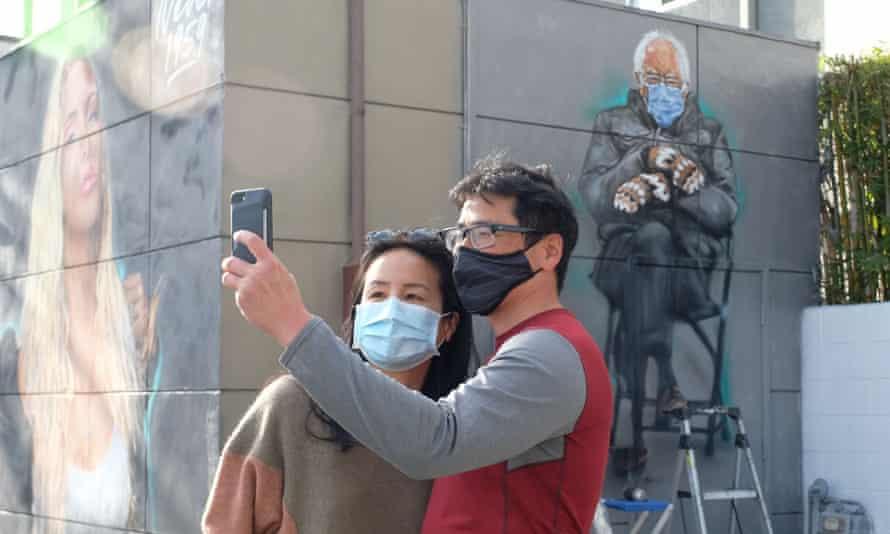 People take a selfie in front of artist Jonas Never's mural of Senator Bernie Sanders in Culver City, California.