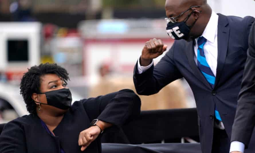 Democratic Senate candidate Raphael Warnock bumps elbows with Stacey Abrams during a rally with Joe Biden in Atlanta.