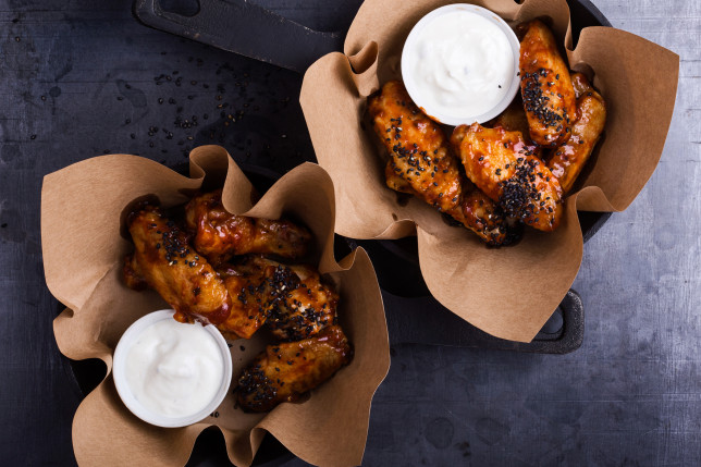 Glazed spicy chicken wings with sesame seeds served in cast iron skillets