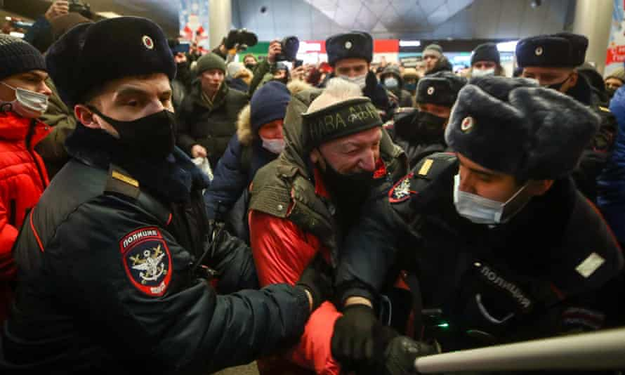 Police officers detain a man at Vnukovo International Airport where Alexei Navalny had been expected to land.